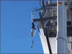 A skier dangles from a chair lift after snagging his backpack